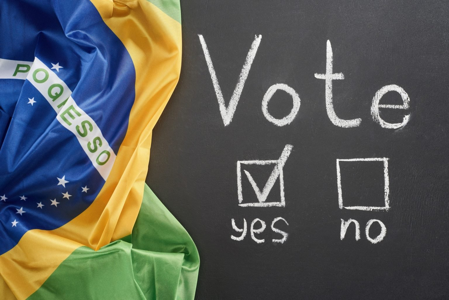 top view of white vote lettering and check mark near yes word on black chalkboard near flag of