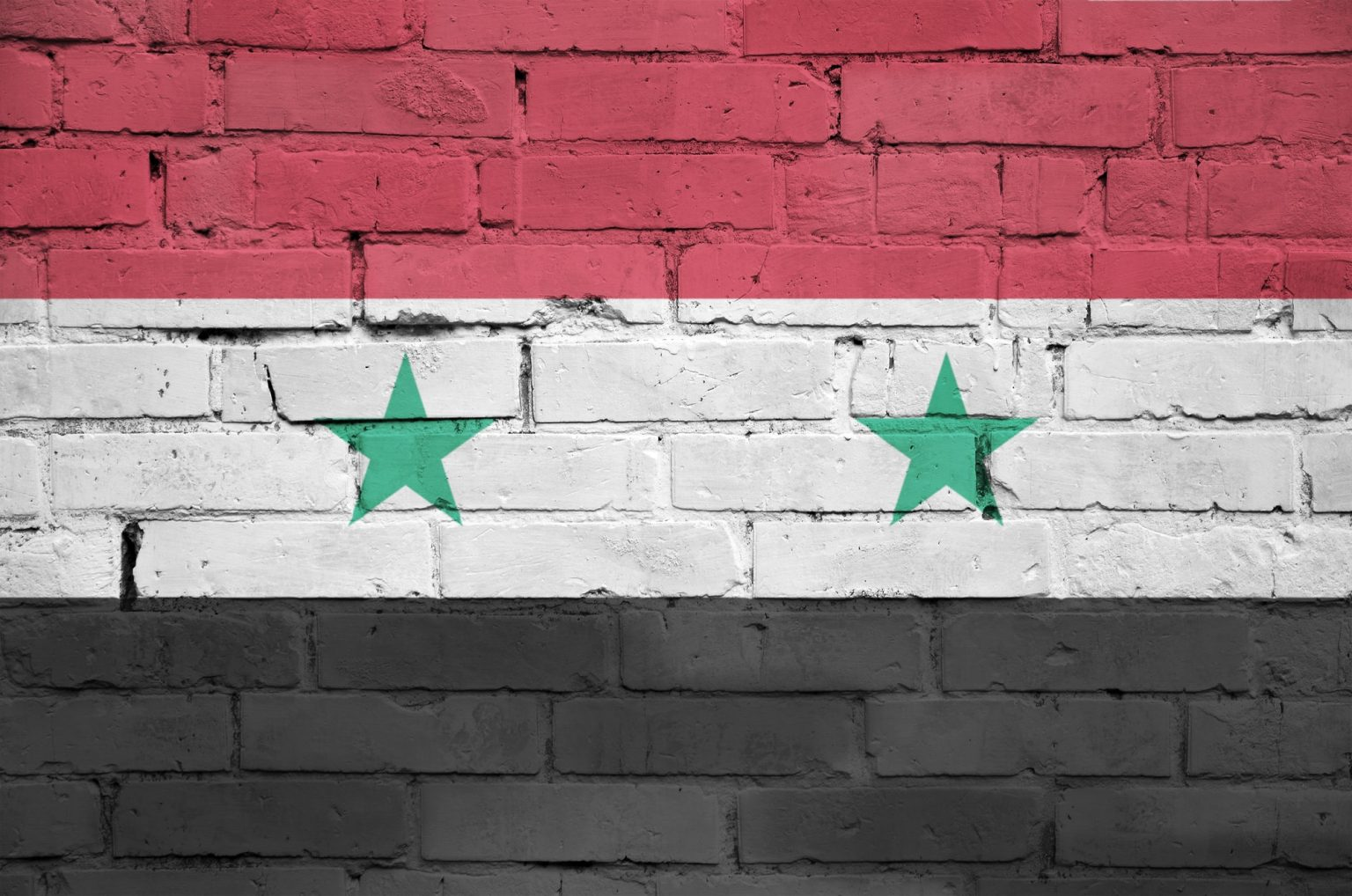 Syria flag is painted onto an old brick wall